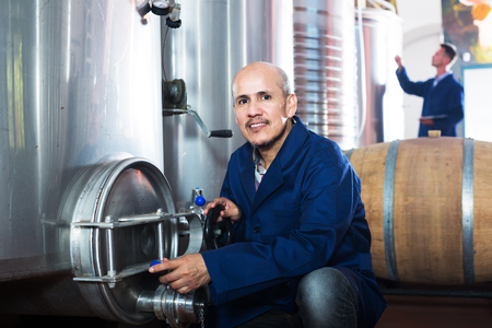 wine register: portrait of positive mature man working in secondary fermenting section  on winery