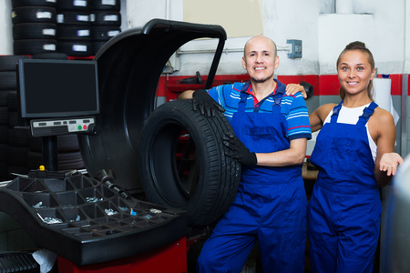 wheel balancing: Two glad technicians working on wheel balancing machinery in car service Stock Photo
