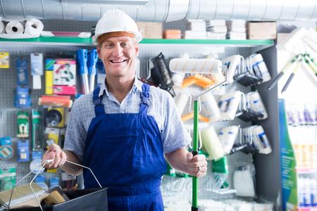 housewares: Portrait of glad workman in uniform choosing soft roller for painting in housewares hypermarket Stock Photo