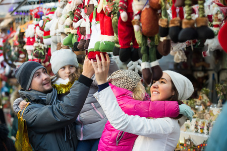 Happy young parents with kids choosing X-mas decorations in market. Focus on woman Stock Photo