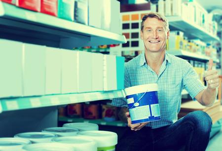housewares: friendly man customer choosing paint bucket in housewares hypermarket