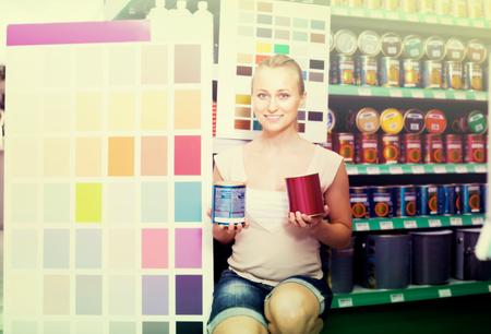 housewares: joyful young woman choosing color for home near color palette in housewares hypermarket