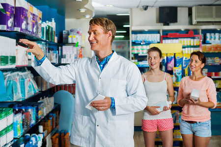 diligente: Friendly diligent man pharmacist wearing uniform and working in pharmaceutical shop