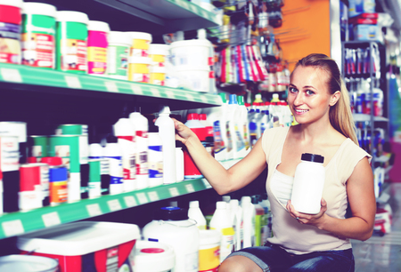 housewares: Portrait of adult female customer taking bottle with paint thinner in housewares department