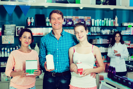Glad family of three persons standing with beauty care products in hands in pharmacy. Focus on man