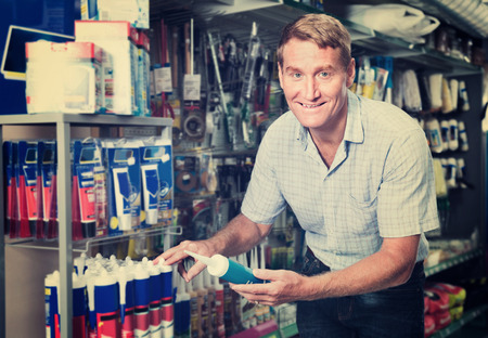 sealant: Portrait of positive cheerful smiling male customer selecting sealant bottle in housewares department