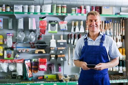 housewares: ?Smiling man seller 40s wearing working overalls standing in housewares supermarket Stock Photo