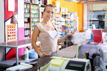 housewares: Glad positive cheerful  female seller standing at pay desk in housewares supermarket