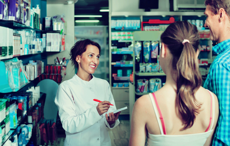 diligente: Smiling diligent positive female pharmacist wearing uniform working in pharmaceutical shop