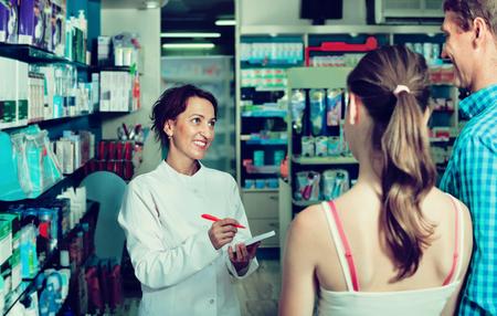 diligente: Sonriendo farmacéutico de sexo femenino con uniforme positivo diligente trabajo en la tienda de productos farmacéuticos