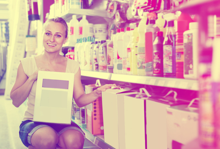 housewares: ?Smiling young woman customer holding box with dry filler in housewares hypermarket Stock Photo