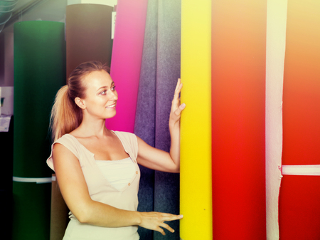 housewares: Positive young woman customer choosing bolt of fitted carpet in housewares hypermarket