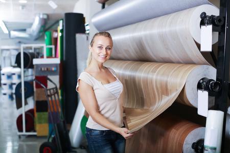 housewares: Glad woman customer choosing linoleum flooring in housewares hypermarket