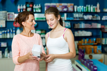 Attractive woman with daughter teenager shopping healthcare products in drug store