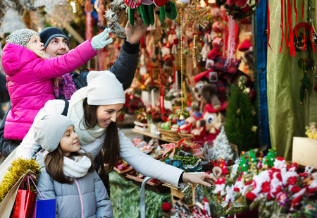 Ordinary family with little girls standing at a coniferous Christmas souvenirs counter. Focus on child in gray clothes Stock Photo