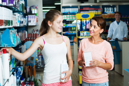 drug store: Positive woman with teenager girl choosing healthcare products in drug store. Focus on girl Stock Photo