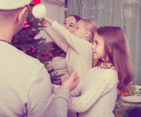 home decorating: Positive family with two little daughters decorating Christmas tree together at home. Focus on girl