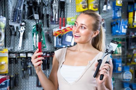 housewares: portrait of cheerful smiling young woman customer choosing pliers in housewares hypermarket Stock Photo