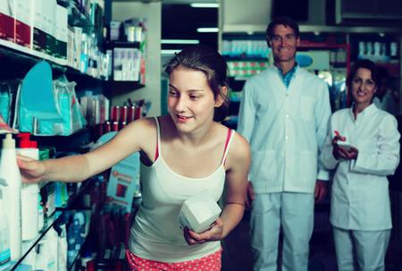 drug store: Positive teenager girl standing with drug store products in hands in drug store