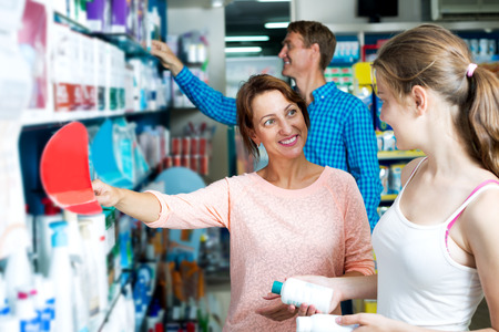 buying questions: Happy woman with young daughter shopping healthcare products in drug store Stock Photo