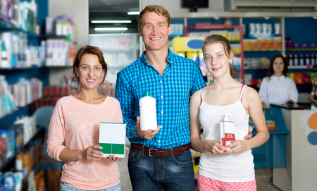 Portrait of glad parents with daughter teenager holding product boxes in hands in drug store