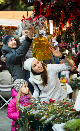 Young positive family of four choosing floral decorations at market. Focus on woman