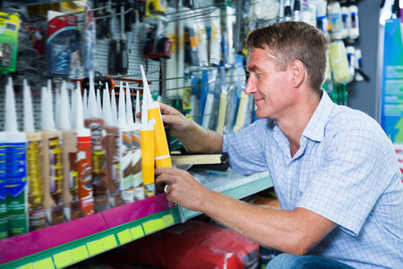 sealant: Smiling man customer picking sealing component in household shop