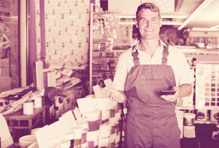 housewares: ?Smiling positive man seller wearing working overalls standing in housewares supermarket Stock Photo