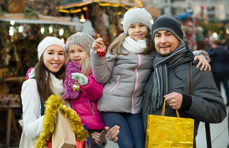 Happy family buying at Christmas market together