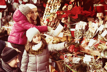 Happy family of four choosing floral decorations at market. Focus on brunette girl Stock Photo