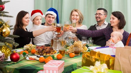granny and grandad: Big family together with mom and dad Celebrating Christmas at festive table Stock Photo