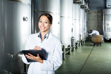 wine register: Cheerful female winery employee in uniform taking off data from equipment in winery fermentation section
