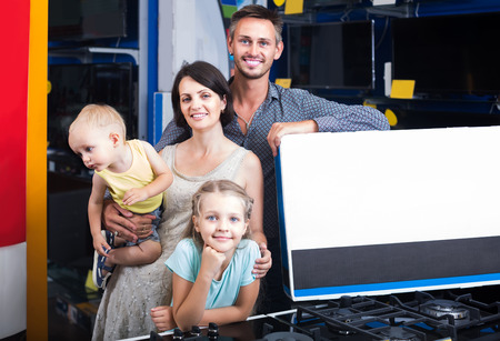 niños de compras: sonrientes padres con dos hijos de compras nueva electrónica y la caja que sostiene en la tienda de electrodomésticos