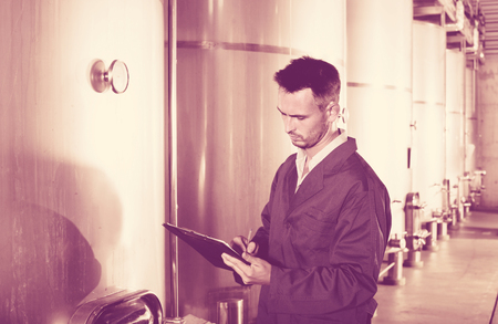 diligente: Portrait of young diligent man wearing coat taking off data from equipment in winery fermentation section