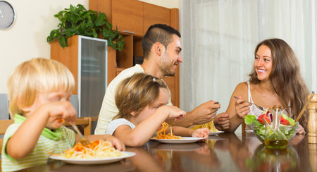 gladful: Positive young family of four eating spaghetti at home interior. Focus on man
