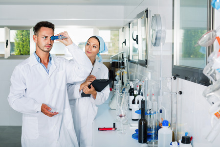 saturation: Two young researchers in white coat checking wine acidity and sugar saturation in chemical laboratory Stock Photo