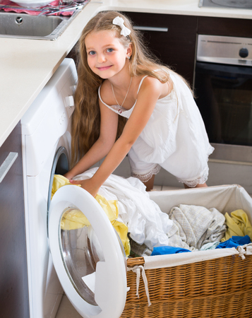 laundry room: Cute smiling little girl loading washing machine in laundry room Stock Photo