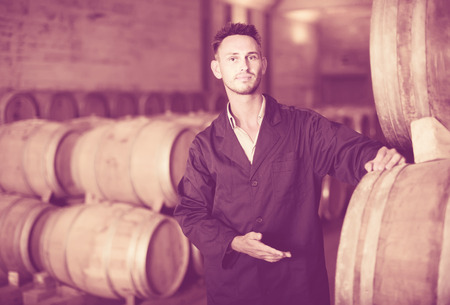 labeling: Young male worker wearing uniform standing and labeling woods in winery cellar