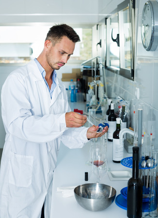 acidity: Young man in white coat checking wine acidity and sugar saturation in chemical laboratory on winery Stock Photo