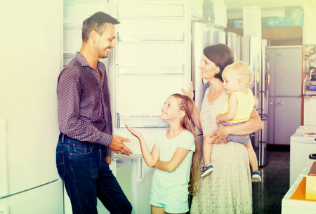 appliances: joyful young parents with two  kids choosing new freezer in shop of household appliances Stock Photo