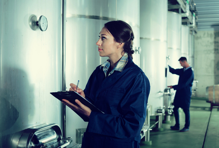 wine register: Adult woman standing with cardboard in hands in fermentation compartment on factory