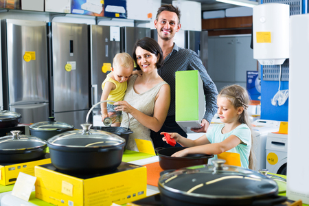 happy family of four shopping new cooking pan in household hypermarket