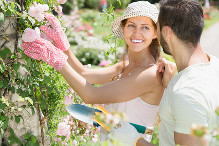 Smiling girl in flowers garden with her boyfriend at summer day