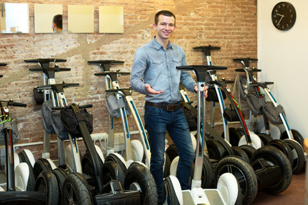 rental agency: Smiling young man with segways at rental agency indoors