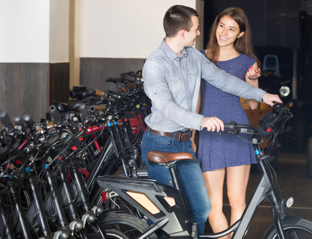 rental agency: positive female employee helping adult guy to select bike at rental agency