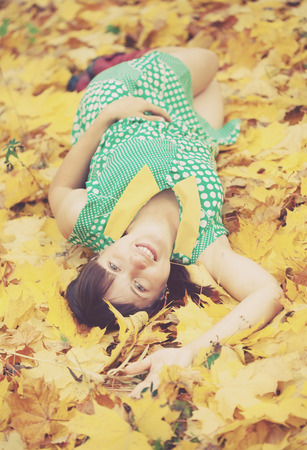 lies down: girl lies in maple leaves at autumn park Stock Photo