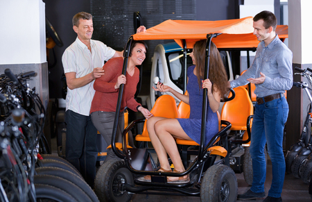 rental agency: Diligent kindly male employee helping family to select tour electrics at rental agency