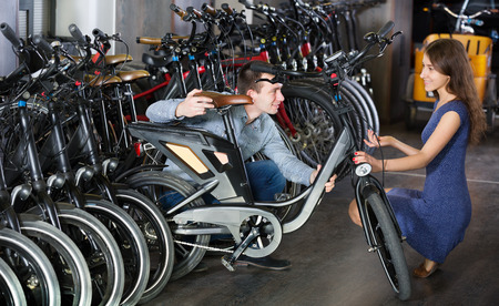 rental agency: Happy young couple selecting bikes in rental agency indoors. Focus on man