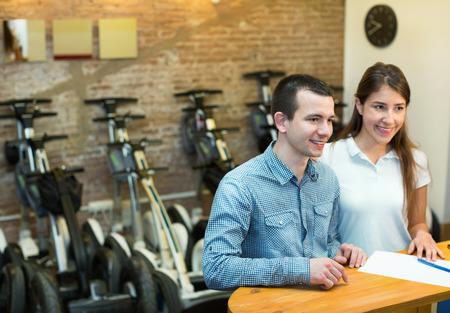 ot: Happy young couple hiring segways ot rental store Stock Photo