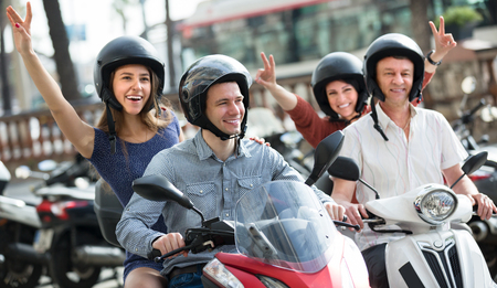 Positive parents and adult children traveling through city by scooters